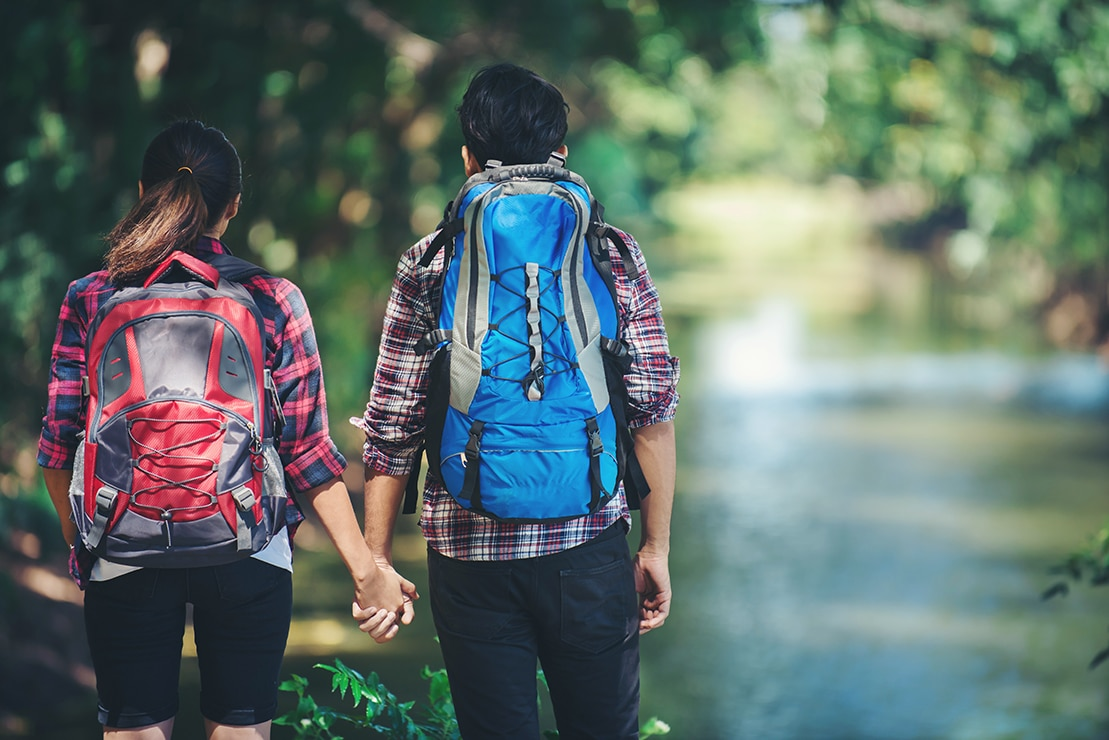 Hiking couple in forest together. Adventure travel vacation. Happy time hiking.